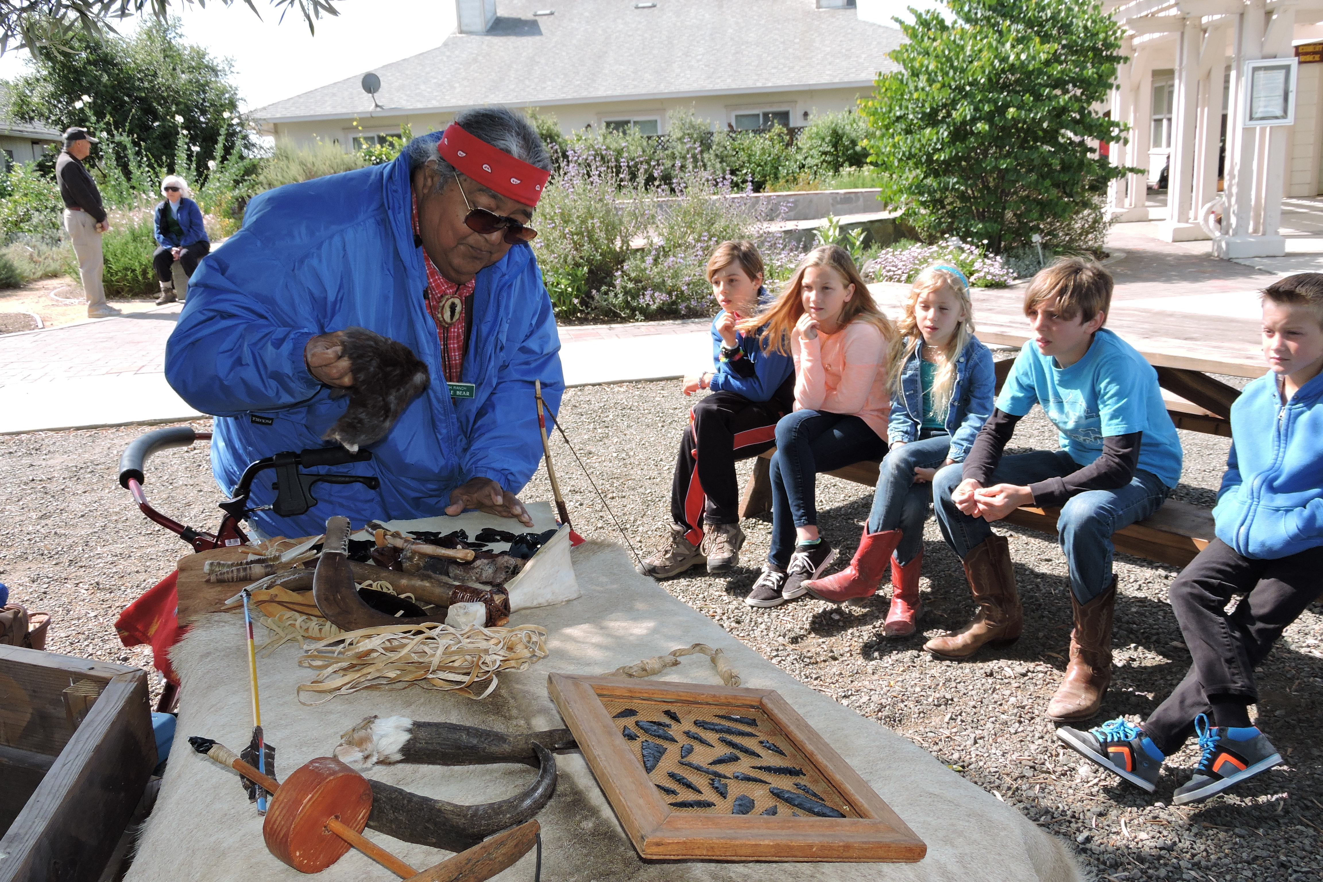 Little Bear, a Rush Ranch volunteer, shows children from Heritage Peak Charter School in Vacaville his collection of Patwin Indian hunting tools and artifacts.